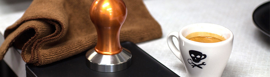 tamping espresso in a portafilter with a tamper from barista basics